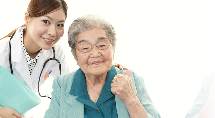 patient doing a OK sign with caregiver leaning on her shoulder